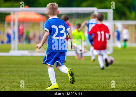 Soccer Kick; Running Soccer Football Players. Footballers Kicking Football Match; Young Soccer Players Running After - Stock Photo