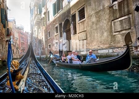 VENICE, ITALY - MAY 21, 2017: Tourists taking a ride on a gondola and beautiful old buildings seen from a gondola - Stock Photo