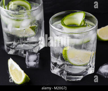 gin tonic with cucumber, lime and ice in glass - Stock Photo