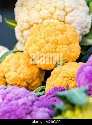 Colorful organic fresh cauliflower displayed at market, closeup. Vivid purple, orange, white cauliflower at market - Stock Photo
