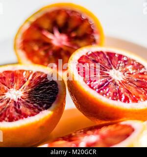 Red blood orange halves, macro food photo, selective focus. Fresh citrus fruit details, closeup, high angle view. - Stock Photo