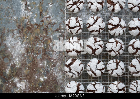 Homemade Chocolate Crinkle Cookies on a cooling rack on slate background - Stock Photo