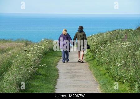 Blue sea beyond, bird watchers (couple) hold hands, carry long lens cameras & walk down path - Bempton Cliffs RSPB - Stock Photo