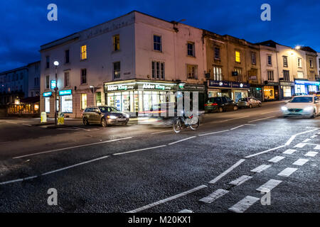 A cyclist waits to turn right in commuter traffic. Whiteladies Road, Bristol, UK. - Stock Photo
