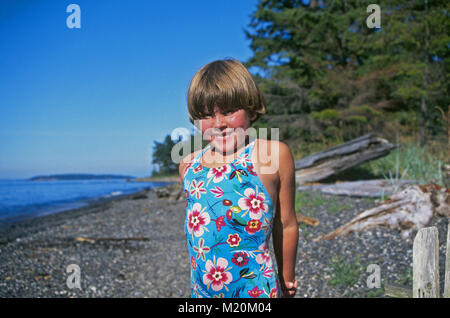 A ten year old girl in a swimming suit on a rocky beach on Lopez Island in the San Juan Islands, Puget Sound, Washington - Stock Photo