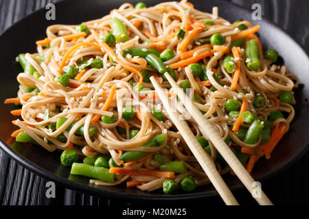 Japanese food: Soba with carrots, peas and green beans close-up on a plate. horizontal - Stock Photo