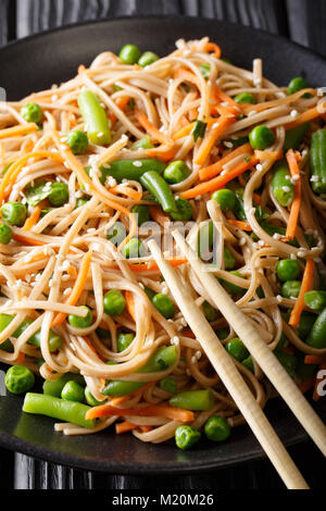 Buckwheat noodles with carrots, peas and green beans close-up on a plate. vertical, japanese style - Stock Photo