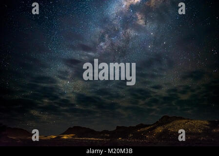 Milky Way arch, stars in the sky, the Namib desert in Namibia, Africa. Some scenic clouds. - Stock Photo