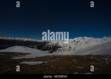 Starry sky night view on the Alps. Snow capped mountain range in moonlight. - Stock Photo