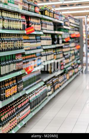 Different types of beer on the shelves in the supermarket - Stock Photo