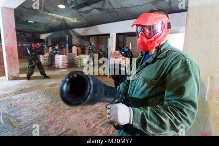 Portrait of red team happy cheerful positive player who is aiming in opponents on paintball field. - Stock Photo