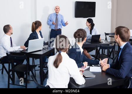 Positive employee in charge presenting report at business meeting in office - Stock Photo