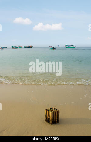 burned firecracker / fireworks in sand on beach with ocean background - - Stock Photo