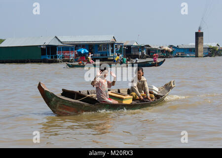Siem Reap, Cambodia - January 2014:  Boy and girl on boat selling drinks on Tonle Sap Lake, Cambodia - - Stock Photo