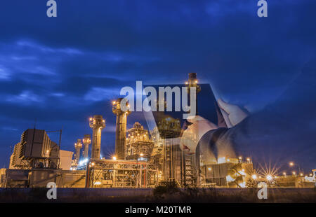 Double exposure of businessman checking oil refinery industry plant by tablet in the night as Energy and Technology - Stock Photo