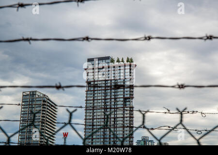 Cityscape of Woodwards behind barbed wire in Vancouver BC. - Stock Photo