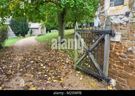 Wooden gate set in a stone wall by a path leading to the secluded church of St Mary The Virgin, Sedgeford, Norfolk, - Stock Photo