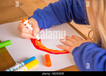 Young girl drawing with bright coloured pens - Stock Photo