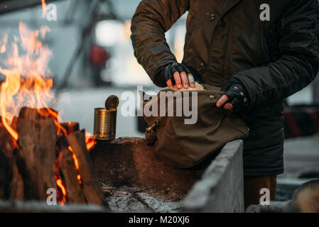 Stalker, male person warms his hands on fire. Post apocalyptic lifestyle with gas mask, doomsday, - Stock Photo