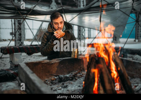 Stalker, male person eating against fireplace. Post apocalyptic lifestyle, doomsday, horror of nuclear war - Stock Photo