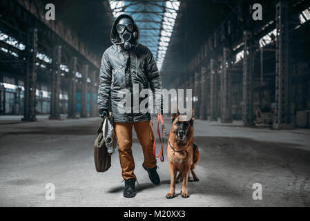 Stalker in gas mask and pet in abandoned building, survivors after nuclear war. Post apocalyptic world. Post-apocalypse - Stock Photo