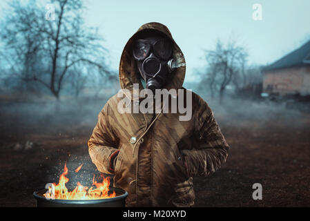 Stalker soldier in gas mask against fire, survivor man after nuclear war. Post apocalyptic lifestyle, doomsday, - Stock Photo