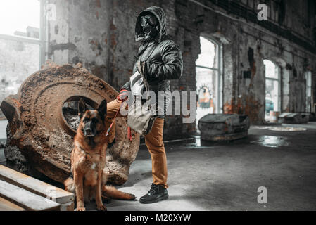 Stalker in gas mask and dog in ruins, survivors in danger zone after nuclear war. Post apocalyptic world. Post-apocalypse - Stock Photo