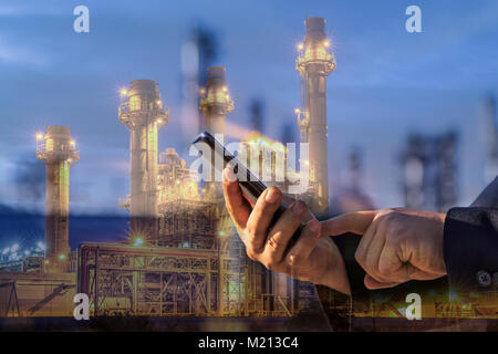 Double exposure of businessman checking oil refinery industry plant by smart phone in the night as Energy and Technology - Stock Photo