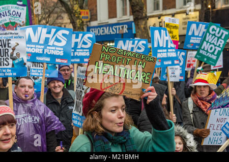 London, UK. 3rd February 2018. A woman holds a poster 'No Space For Profit In Healthcare' on the march by tens of - Stock Photo