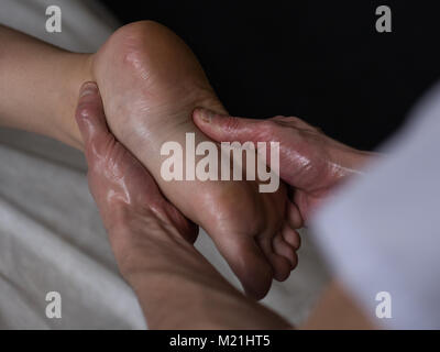 Beautiful young woman reciving relxing Foot Massage from Professional Masseur - Stock Photo