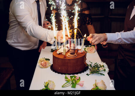 Birthday cake with fireworks on table in black background Stock