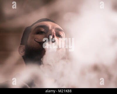 Man with Beard and Mustages Vaping an Electronic Cigarette. Vaper Hipster Smoke Vaporizer and Exhals Tight Smoke. - Stock Photo