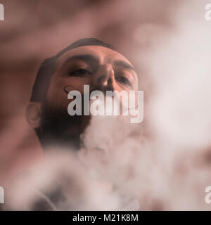 Man with Beard and Mustages Vaping an Electronic Cigarette. Vaper Hipster Smoke Vaporizer and Exhals Smoke Rings. - Stock Photo