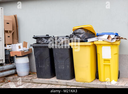 Overflowing plastic waste cans with black garbage bags, cardboard boxes and a container with a liquid - Stock Photo
