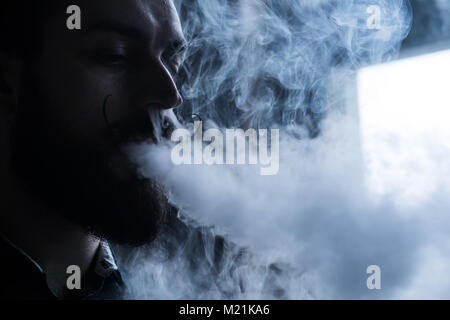 Man with Beard and Mustages Vaping an Electronic Cigarette. Vaper Hipster Smoke Vaporizer and Exhals Smoke Flow. - Stock Photo