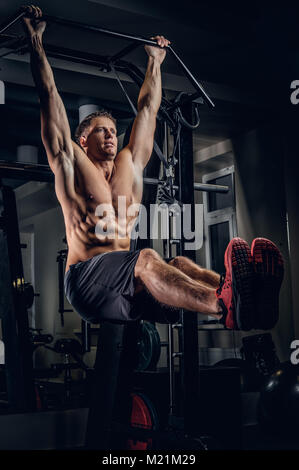 A man doing ABS workouts on pull up bar. - Stock Photo