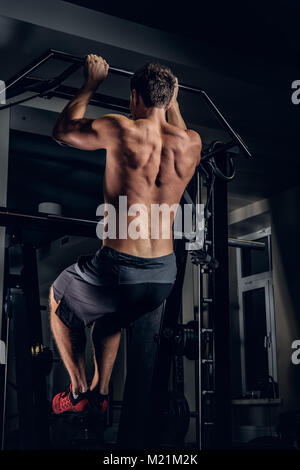 A man doing pull ups on the horizontal bar. - Stock Photo