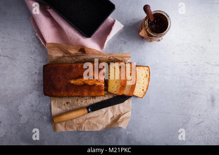 Homemade pound cake on baking paper served with fruit jam ready to eat, top view - Stock Photo