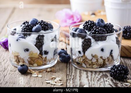Healthy breakfast with homemade granola and fresh berries, yogurt with muesli, dried fruits, blueberries and blackberries - Stock Photo