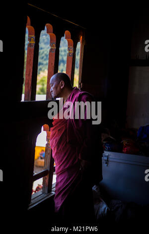 Prakhar Lhakhang, Bumthang, Bhutan.  Buddhist Monk Watching Religious Dancing from a Window in the Monastery. - Stock Photo