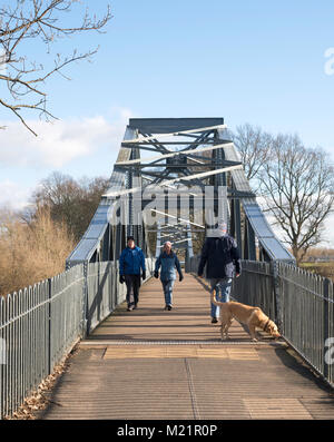 Couple with dog walking across Rickerby Park memorial footbridge over the river Eden in Carlisle, Cumbria, England, - Stock Photo