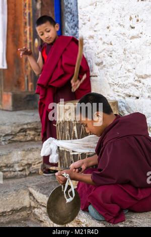 Prakhar Lhakhang, Bumthang, Bhutan.  Two Young Monks Playing Drum and Gong. - Stock Photo