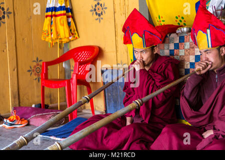Prakhar Lhakhang, Bumthang, Bhutan.  Buddhist Monks Playing the Dungchen (Long Trumpet). - Stock Photo