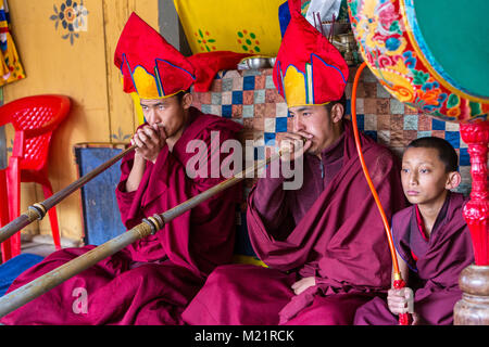 Prakhar Lhakhang, Bumthang, Bhutan.  Buddhist Monks Playing the Dungchen (Long Trumpet), Young Monk Playing the - Stock Photo
