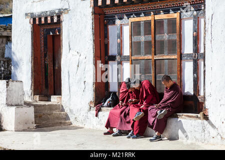 Prakhar Lhakhang, Bumthang, Bhutan.  Young Monks Looking at their Cell Phones. - Stock Photo