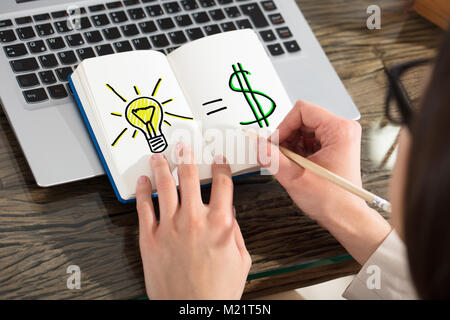 Business Woman Drawing A Idea For Making Money With Pencil On Notebook Over The Laptop - Stock Photo
