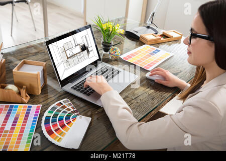 An Female Architect Working On Color Selection For The Kitchen Drawing On Laptop Screen - Stock Photo