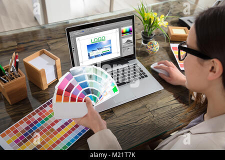 A Woman Holding Color Swatches Using A Laptop With Logo Design Software On The Screen - Stock Photo