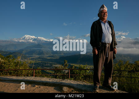 Local Nepalese older man standing with Annapurna mountain range behind - Stock Photo