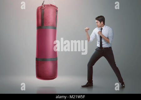 Young asian businessman punching boxing bag over gray background - Stock Photo